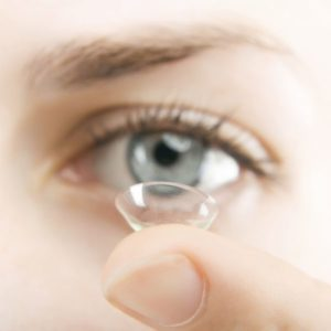 Contact lens on top of finger with person's eye in the background